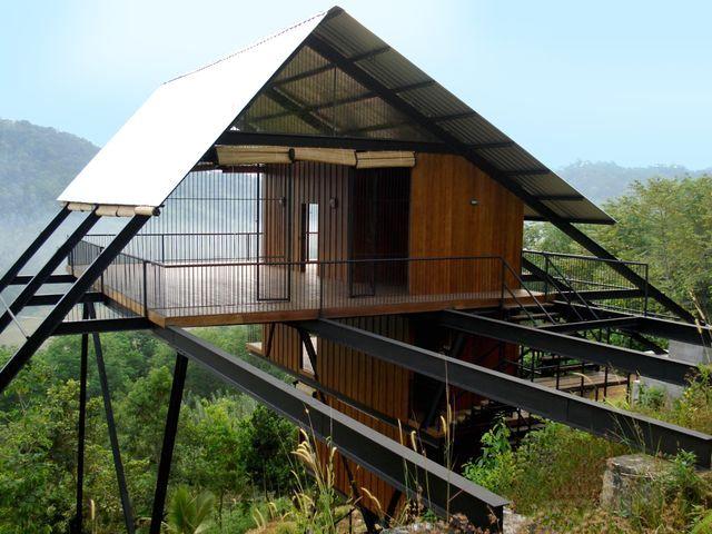 деревянный дом на сваях над деревьями в джунглях