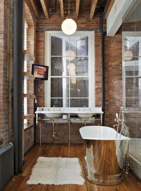 интерьер ванной комнаты в индустриальном стиле с золотистой ванной